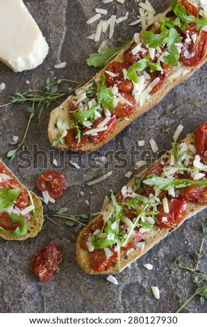 Bruschetta with roasted cherry tomatoes, rocket and Parmesan - stock photo