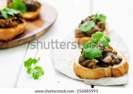 bruschetta with roasted mushrooms on a white wood background. tinting. selective focus