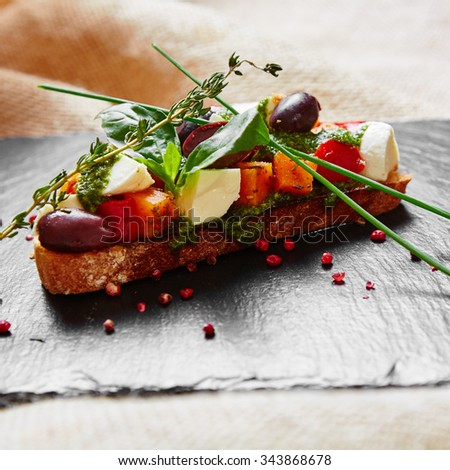 Bruschetta with roasted pumpkin, red pepper,pesto and cheese - stock photo