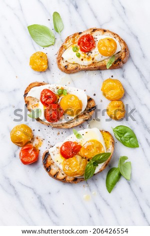 Bruschetta with roasted tomatoes and mozzarella cheese on grilled crusty bread on white marble - stock photo
