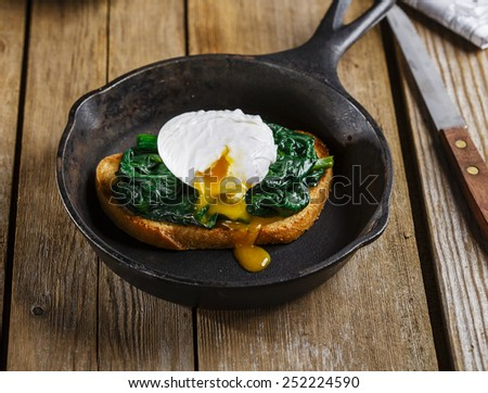 Bruschetta with spinach and poached egg - stock photo