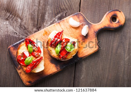 Bruschetta with sun dried tomatoes, basil leaves and garlic - stock photo