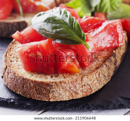 Bruschetta with tomato and basil over black stone - stock photo