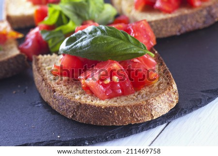 Bruschetta with tomato and basil over black stone plate, close up - stock photo