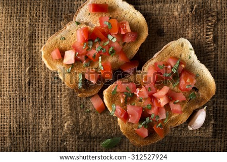 Bruschetta with tomato and basil over old canvas bag and copy space - stock photo