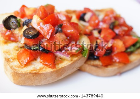 Bruschetta with tomato and olives - stock photo
