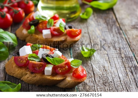 bruschetta with tomato, feta cheese, olives and basil - stock photo