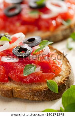 Bruschetta with  tomato, olives, onion and oregano - stock photo