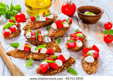 bruschetta with tomatoes, mozzarella and basil on fried in olive oil rye baguette with seeds, on parchment paper. ingredients on peeling paint white planks, italian recipe, close-up, top view