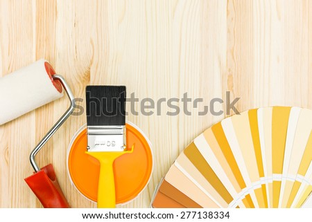 brush and roller with color guide and paint can on wooden background - stock photo