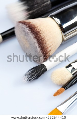 Brush away your flaws. Studio shot of a set of makeup professional different sizes make-up brushes spread out against a white background - stock photo