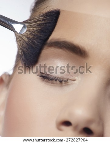 Brush blusher spreading liquid cosmetic powder on face and eyes (shallow focus) - stock photo