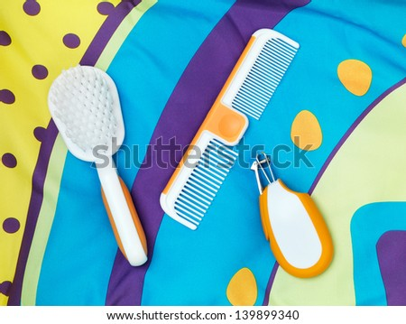 Brush, comb, nail clippers, set of baby grooming accessories on colorful fabric - stock photo