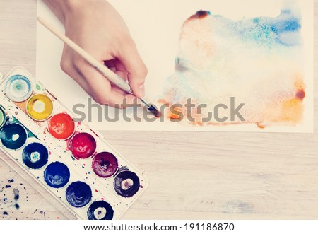 brush in the hands of the artist, watercolor painting, creativity, with retro instagram effect - stock photo