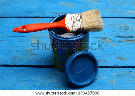 brush painting on tin can of blue paint - stock photo