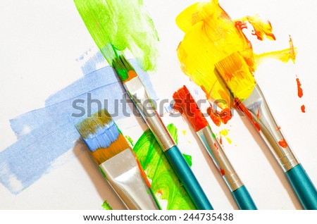 brush strokes and paint brushes on white paper background - stock photo