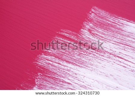Brush strokes of white paint across half a deep pink wooden surface - stock photo