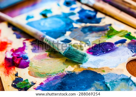 Brush with paint on canvas - stock photo