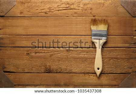 Brush with paint on rustic wooden background with copy space.