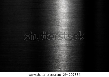 Brushed metal texture in the dark with intense narrow lighting in middle.  - stock photo