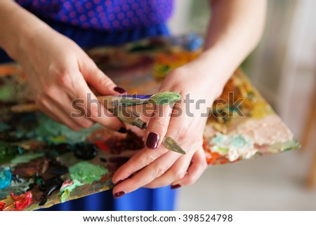 brushes and oil paints on palette. texture mixed oil paints in different colors. palette with paintbrush and palette-knife in hands. The artist holding a palette with paints, brush and palette knife - stock photo