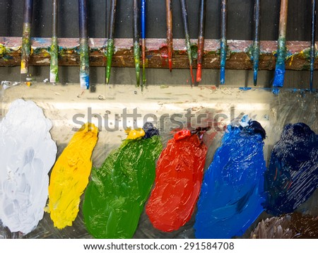 Brushes and paints on the working place of decorator - stock photo