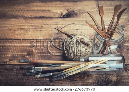 Brushes and sculpturing tools on rustic wooden background. - stock photo