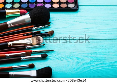Brushes for makeup on blue wooden background. Top view and selective focus - stock photo