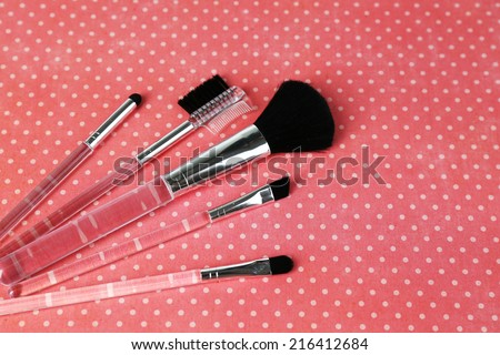 Brushes for makeup on pink background - stock photo