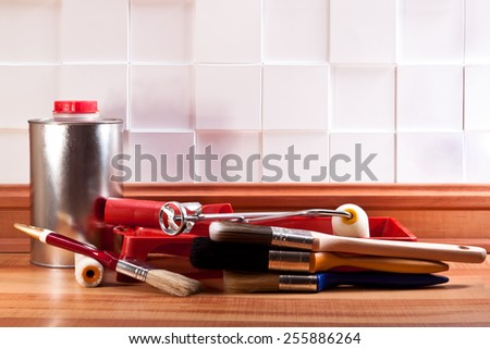 Brushes for paint rollers, mixer, and the solvent on the floor - stock photo