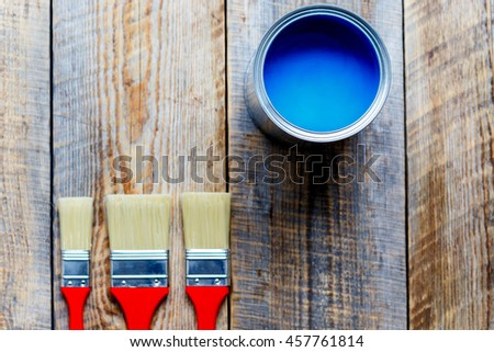 brushes on wooden floor with jar of paint top view