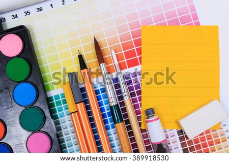 Brushes, watercolor, eraser, paper note and abstract colored palette guide.