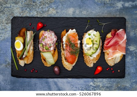 Brushetta or authentic traditional spanish tapas set for lunch table. Sharing antipasti on party or summer picnic time over blue rustic background. Top view, flat lay.