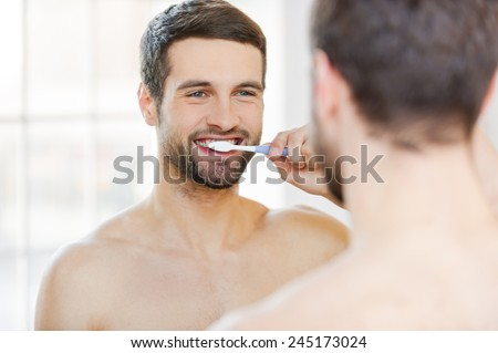 Brushing teeth in the morning. Rear view of handsome young beard man brushing his teeth and smiling while standing against a mirror - stock photo
