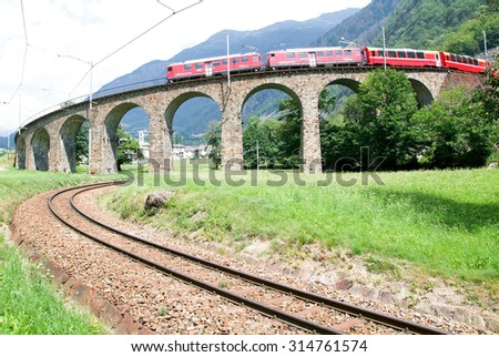 Brusio, Switzerland - 20  July 2007: Bernina Express Train at the circular Viaduct of Brusio on the Swiss alps. Unesco world heritage site