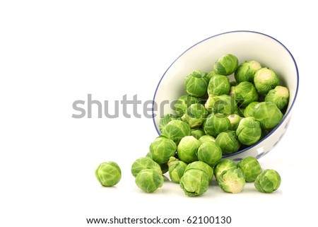 Brussel sprouts coming from a decorated bowl on a white background - stock photo