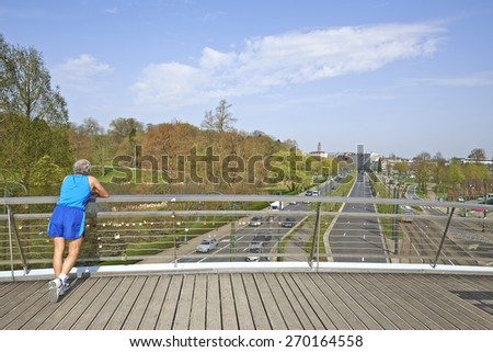 BRUSSELS, BELGIUM - APRIL 16, 2015: Senior Man Resting on the bridge at the Tervueren avenue in Brussels, Belgium. This metal pedestrian bridge overcomes the Avenue de Tervuren - stock photo