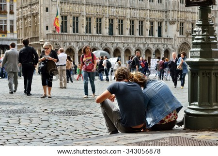 BRUSSELS, BELGIUM-AUGUST 29, 2015: Couple of tourists sitting on the pavement of Grand Place in Brussels having pause between excursions - stock photo