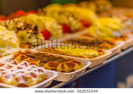 BRUSSELS, BELGIUM - 11 AUGUST, 2015: Famous belgian waffles as displayed in store with cream, berries and chocolate sauce. - stock photo