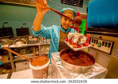 BRUSSELS, BELGIUM - 11 AUGUST, 2015: Happy lady working in belgian waffle store showing how to prepare and decorate this wonderful famous sweet experience. - stock photo