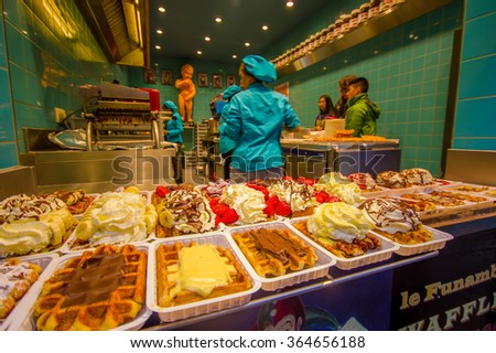 BRUSSELS, BELGIUM - 11 AUGUST, 2015: Inside a belgian waffle store, many delicious plates lined up with different toppings such as chocolate, cream, berries and caramel - stock photo