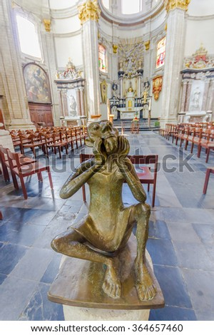 BRUSSELS, BELGIUM - 11 AUGUST, 2015: Inside famous Our Lady of Assistance Church, showing beautiful white stone and concrete architecture, artistic bronze statue with altar visible at the end - stock photo