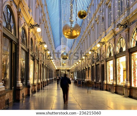 BRUSSELS, BELGIUM-DECEMBER 8, 2014: People cross decorated for Christmas Royal Galleries Saint Hubert in the morning visible as blurred silhouettes. The Galleries are one of main attractions of city - stock photo