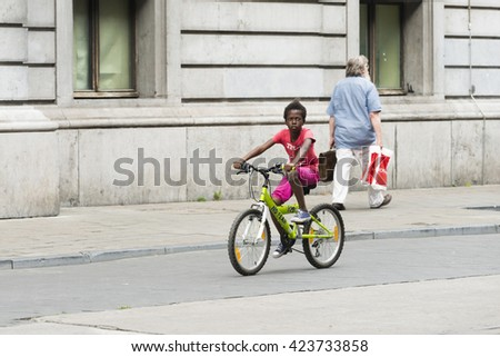 BRUSSELS, BELGIUM - JULY 4, 2015: A black boy rides his bike along one of the streets of the city. - stock photo