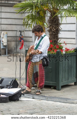 BRUSSELS, BELGIUM - JULY 4, 2015: A man plays guitar on the street to earn some coins from passersby. - stock photo