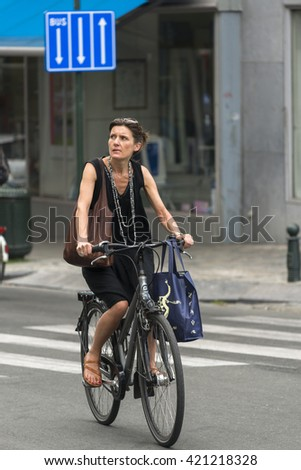 BRUSSELS, BELGIUM - JULY 4, 2015: A woman riding her bicycle, carrying a bag, walks through one of the streets of the city. - stock photo