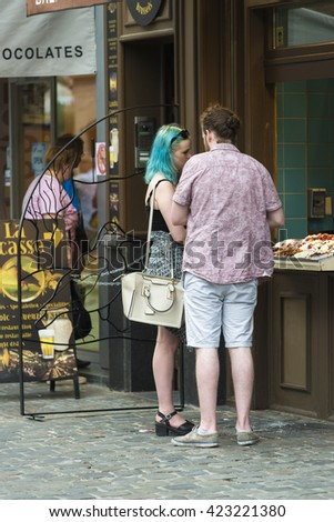 BRUSSELS, BELGIUM - JULY 4, 2015: A young couple buying something to eat at one of the many shops of prepared food. - stock photo