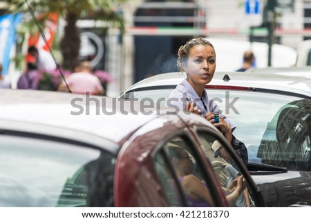BRUSSELS, BELGIUM - JULY 4, 2015: A young woman with wet hair and towel over her shoulders, smoking a cigar on the street. - stock photo