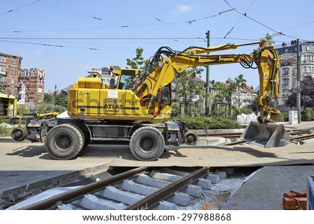 BRUSSELS, BELGIUM -16 JULY 2015: bulldozer on construction site and some workers repair and replace rail trams in Brussels at Verboekhoven square in Schaerbeek. - stock photo