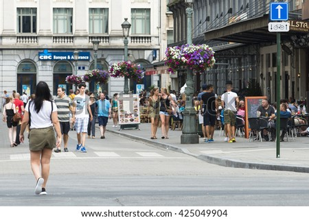 BRUSSELS, BELGIUM - JULY 4, 2015: Detail of one of the central streets of the city, full of people walking and sitting on the terraces of cafes. - stock photo